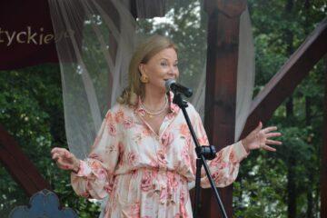Kobieta (Laura Łącz - aktorka, pisarka, reżyserka) przed mikrofonem wykonuje utwór muzyczny na scenie przy Muzeum Michała Kajki w Ogródku